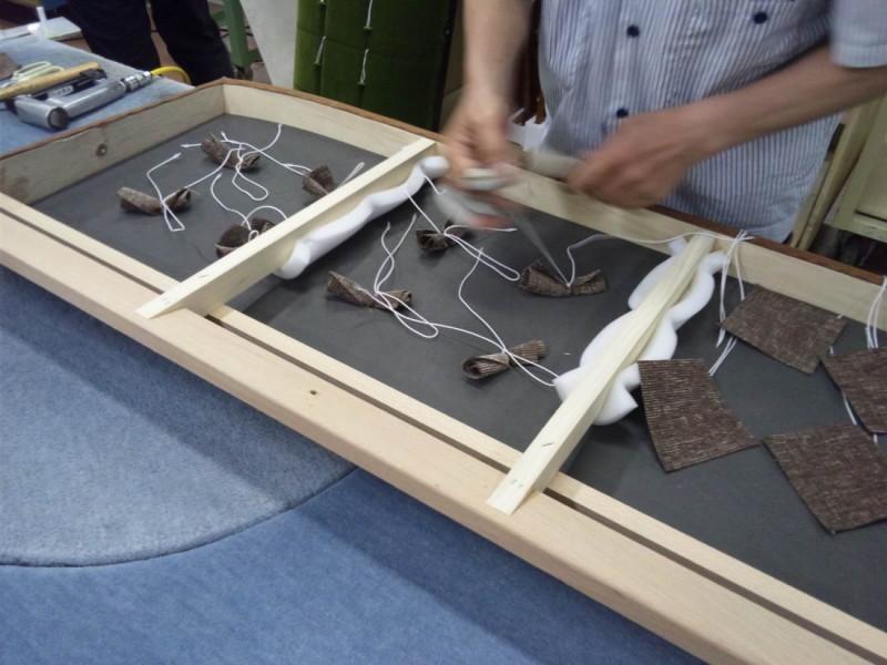 Kチェア2シーター本革の座面のボタンを手作業で取り付けする風景